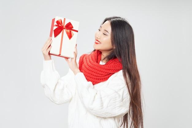 선물 상자와 목에 빨간 스카프를 두른 아름다운 아시아 여성