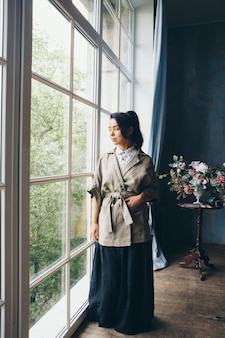 Beautiful asian woman with a hairstyle in japanese style and a kimono at the window on the background of the home interior