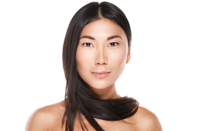 Beautiful asian woman with a healthy black hair on white wall