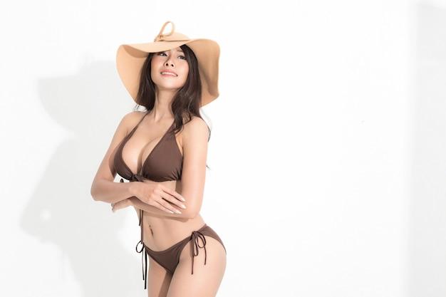 白い背景と影で隔離の夏のファッションポーズスタジオショットで茶色のビキニドレスと日よけ帽を身に着けている長い茶色の髪を持つ美しいアジアの女性。