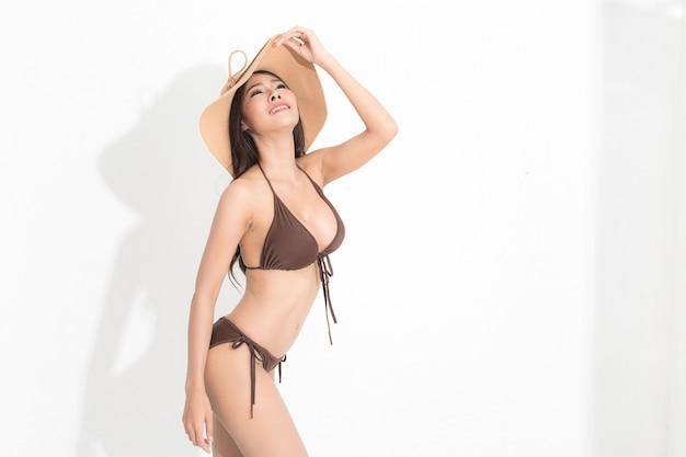 白い背景と影で隔離のスタジオショットをポーズする夏のファッションで茶色のビキニドレスと日よけ帽を身に着けている長い茶色の髪を持つ美しいアジアの女性。