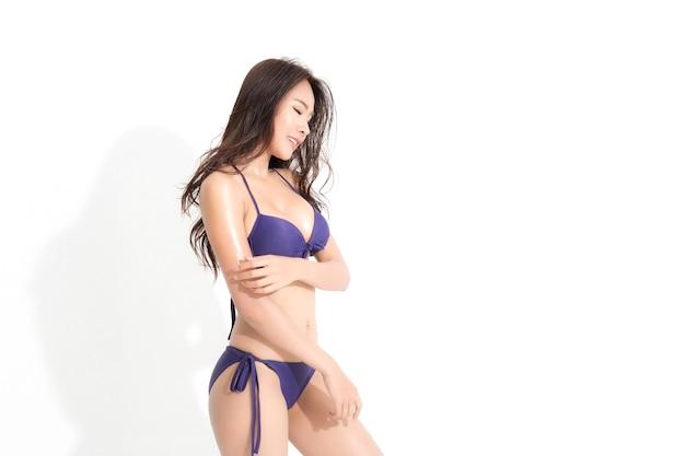 白い背景と影で隔離のスタジオショットをポーズする夏のファッションで紫色のビキニドレスを着て長い茶色の髪を持つ美しいアジアの女性。