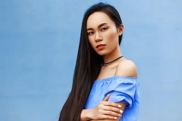 明るい青い壁の近くに立っている青いブラウスの長い髪の美しいアジアの女性