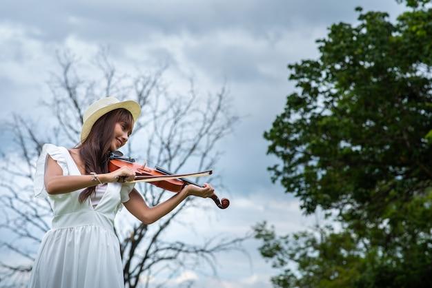 Красивая азиатская женщина с длинными волосами играет на скрипке