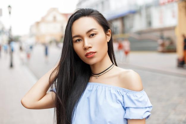 都市でポーズをとる長い髪の美しいアジアの女性。