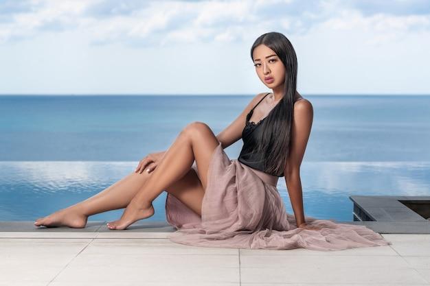 인피니티 풀의 가장자리에 포즈를 취하는 긴 머리를 가진 아름 다운 아시아 여자
