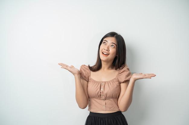 Красивая азиатская женщина с длинными волосами усмехаясь пока поднимающ ее руку против