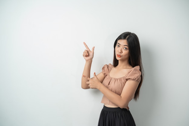 Beautiful asian woman with long hair standing up while gesturing with pointed hands against