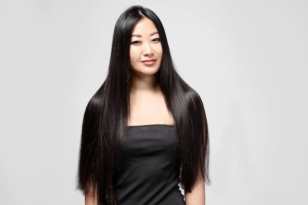 Красивая азиатская женщина с длинными прямыми волосами на светлом фоне
