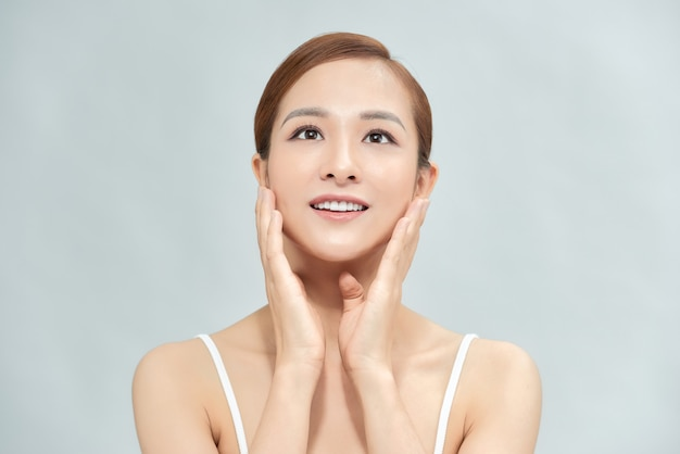 完璧なメイクと色の背景に分離された滑らかな肌を持つ美しいアジアの女性。フェイシャルビューティー整形手術のコンセプト。