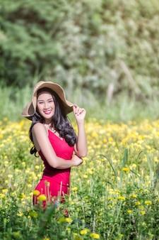 금 잔 화 꽃밭에 빨간 드레스와 함께 아름 다운 아시아 여자
