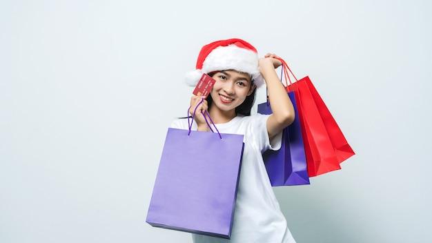 スタジオショットで買い物袋とクレジットカードを保持しているサンタの帽子を持つ美しいアジアの女性。