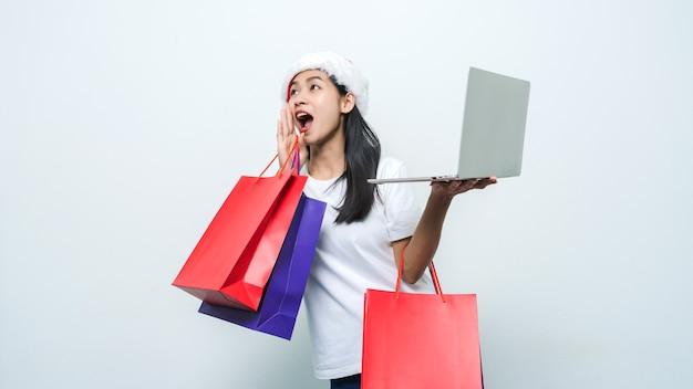 スタジオショットで買い物袋とラップトップを保持しているサンタの帽子を持つ美しいアジアの女性。