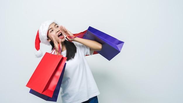 スタジオショットで買い物袋を保持しているサンタ帽子を持つ美しいアジアの女性。