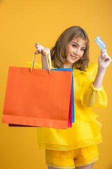 ショッピングバッグとクレジットカードを手に持つ美しいアジアの女性 無料写真