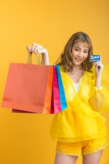 Beautiful asian woman with shopping bag and credit card in hand