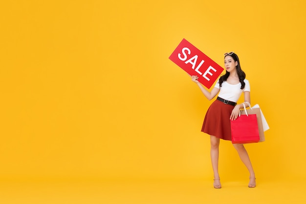 Beautiful asian woman with shopping bags showing red sale sign