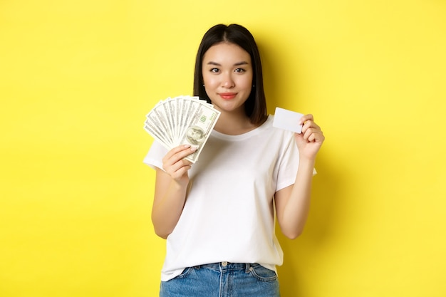 Beautiful asian woman with short dark hair, wearing white t-shirt, showing money in dollars and plastic credit card, standing over yellow background.