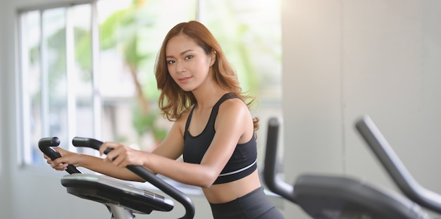 Beautiful asian woman with slim body doing cardio workout on elliptical machine
