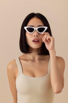Красивая азиатская женщина с солнцезащитными очками позирует
