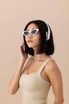선글라스 포즈와 함께 아름 다운 아시아 여자