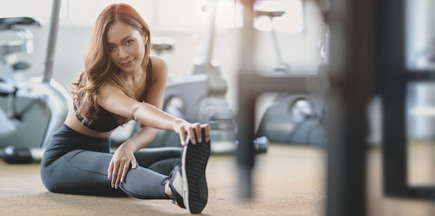 Beautiful asian woman with tan and slim body stretching legs before exercise