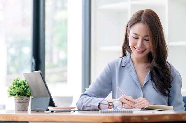 거실에 있는 테이블에 앉아 흰색 컴퓨터를 사용하고 노트북에 글을 쓰는 아름다운 아시아 여성은 가정 개념에서 일합니다.