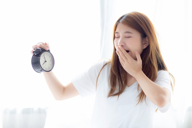 Beautiful asian woman yawn wake up in morning annoyed alarm clock