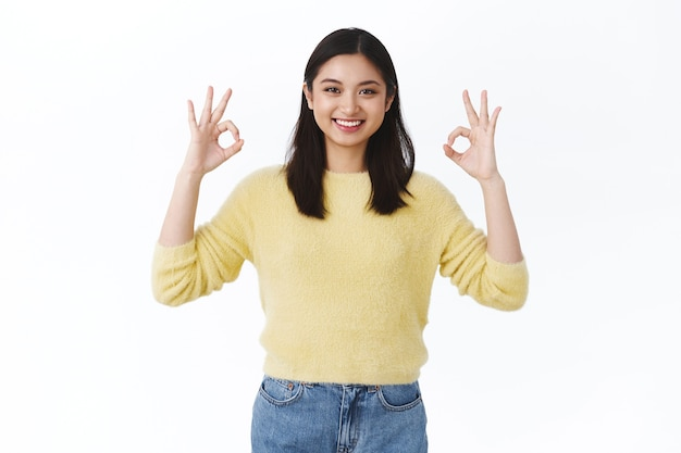 Beautiful asian woman in yellow sweater showing okay gesture and smiling satisfied, recommend great service, saying all good, alright, agree with friend, smiling