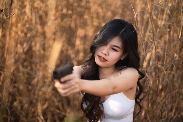 Beautiful asian women aim the gun on dry grass