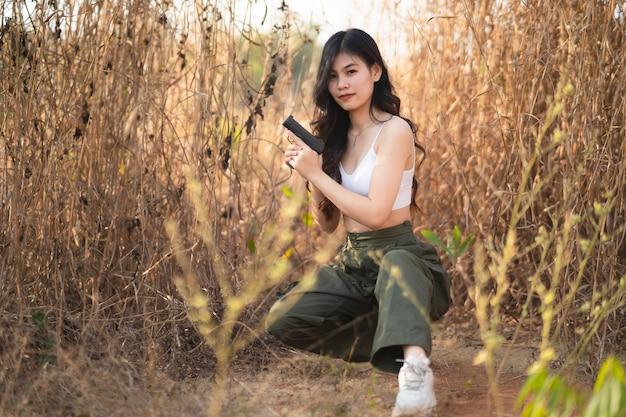 Beautiful asian women aim the gun on dry grass
