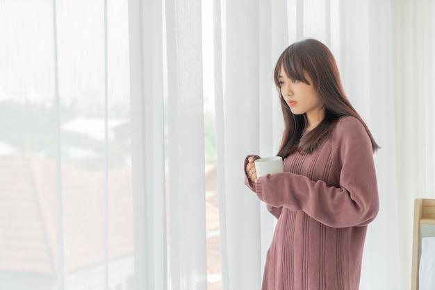 朝コーヒーを飲む美しいアジアの女性