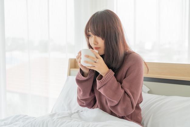 朝のベッドでコーヒーを飲む美しいアジアの女性