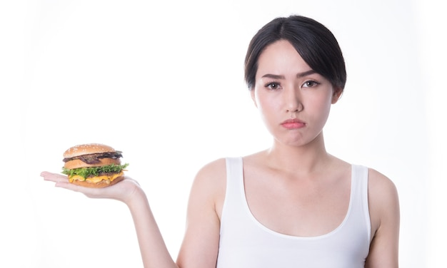 Beautiful asian women eating burger isolated. fast food