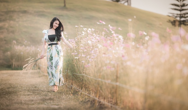 Beautiful asian women girl walking and smiling relax in the park flower picture style vintage