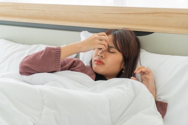 美しいアジアの女性の頭痛とベッドで寝ています。