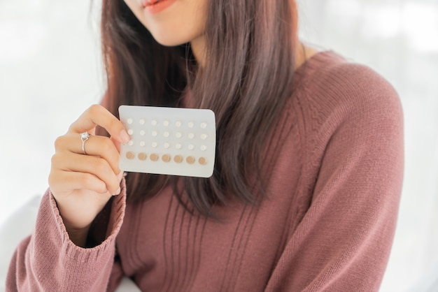 経口避妊薬を保持している美しいアジアの女性