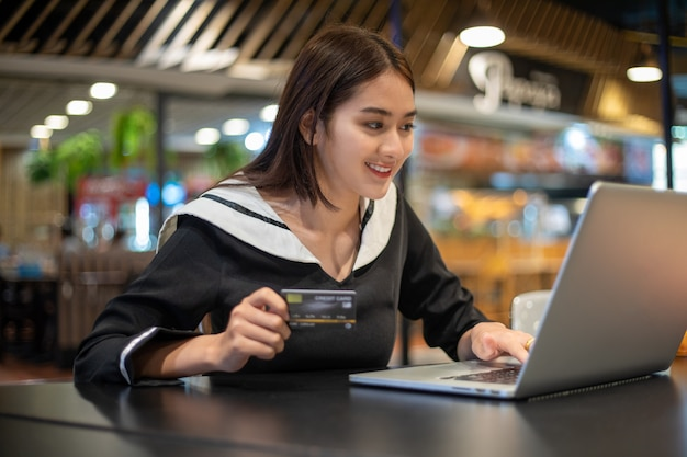 Beautiful asian women holding credit card and mobile phone for shopping online.she smiling and happy