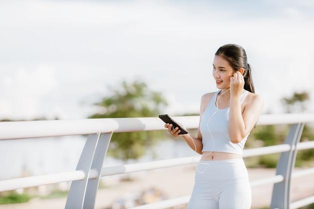 スポーツウェアの美しいアジアの女性公園で屋外の運動中に音楽を聴いています。健康な女性の概念。ランニングトレーニング。