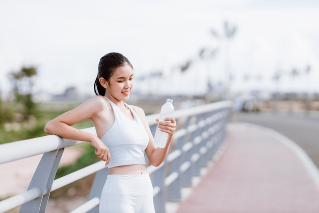 Красивые азиатские женщины в спортивной одежде, стоя на открытом воздухе, держа бутылку с водой для питья после тренировки. концепция здоровых женщин. беговая тренировка.