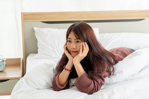 Beautiful asian women lying on bed in the morning