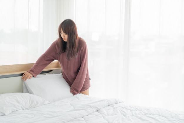 Beautiful asian women making bed in room with white clean sheet