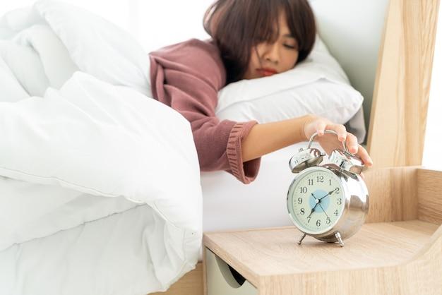 Красивые азиатские женщины на кровати и просыпаются утром