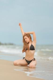 美しいアジアの女性またはタイの女性とビーチでの黒のビキニ
