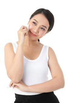 아름다운 아시아 여성의 피부 치료, 스폰지를 사용하여 얼굴, 아름다움, 미소를 지으며 매력적입니다. 흰 바탕