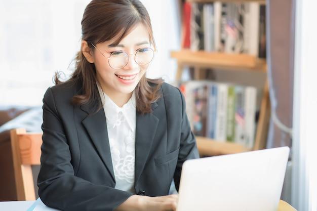 아름다운 아시아 여성, 태국 여성은 아침에 노트북 컴퓨터에서 양복과 미소와 키보드를 행복하게 착용합니다.