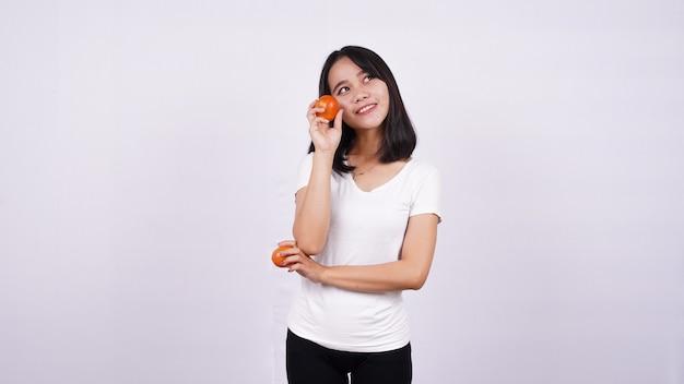 白い表面に分離されたトマトで考える美しいアジアの女性