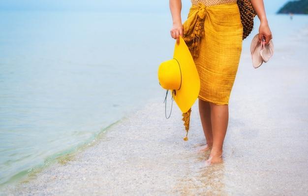 美しいアジアの女性は夏にビーチで旅行します。海砂の太陽と休暇。