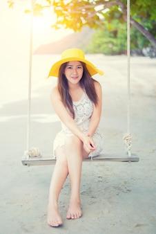 美しいアジアの女性は夏にビーチで旅行します。海砂の太陽。休日と休暇の概念。