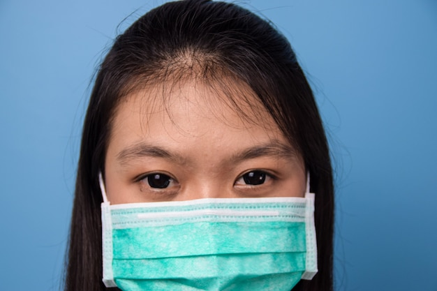 青い孤立した背景を持つ白いtシャツを使用して美しいアジアの女性マスクcovid19を使用して女性